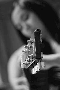 Tjej med gitarr. Foto: Lauren Rabaino, stock.xchng