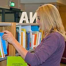 Bibliotekarien Eva Akne plockar fram böcker ur hylla på Infoteket om funktionshinder.
