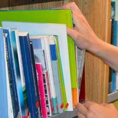 Händer som plockar fram böcker ur en bokhylla.