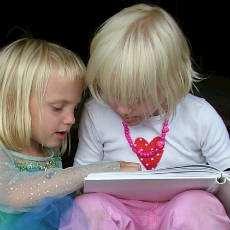 Två flickor som läser en bok.