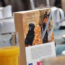 En bok bland kaffekoppar och glas.