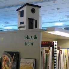En fågelholk i form av ett hus p bokhyllan för böcker med tema hus och hem.