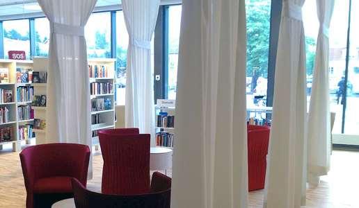 Interiör från Knivsta bibliotek med röda stolar och vita draperier.