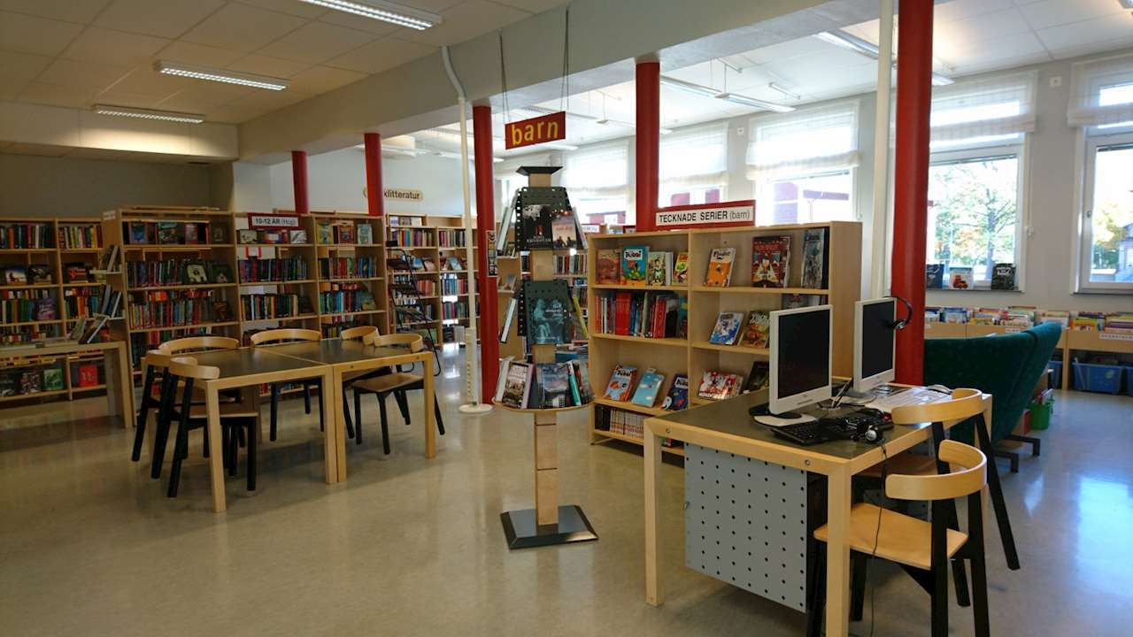 Bokhyllor med böcker samt bord och stolar och skyltningshylla.