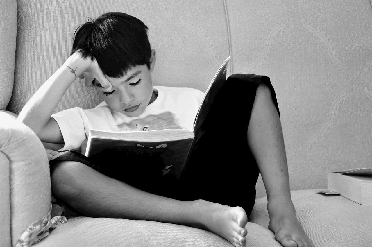 Barn sitter i soffa och läser i en bok